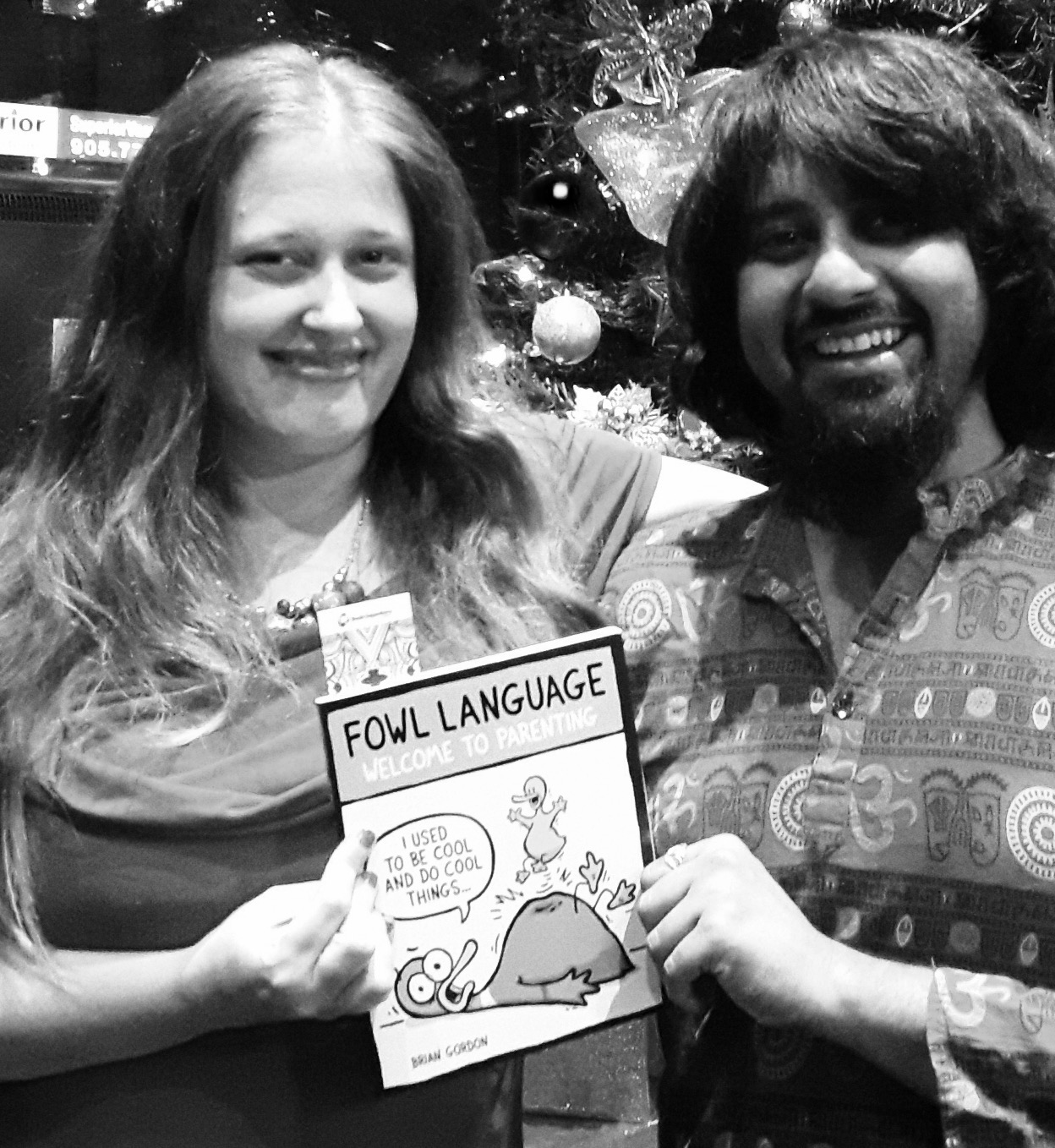 Shyam and Tessa holding the book Welcome to Parenting